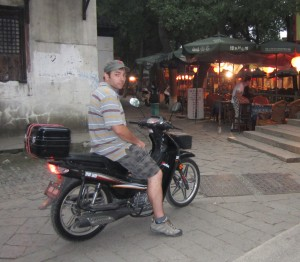 Michael Collier riding a scooter through Tongli